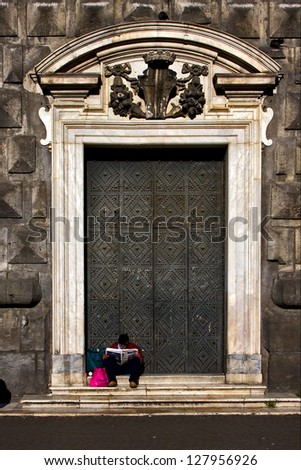 the brown gate  in the church gesu nuovo in naples and a homeless reading a newspaper - stock photo