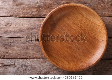 The brown wooden plate on a rustic table closeup. horizontal top view  - stock photo