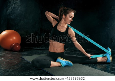 The brunette athletic woman exercising with rubber tape - stock photo