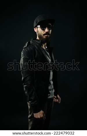 The brutal bearded man in a black fitted hat is standing, fists clenched - stock photo