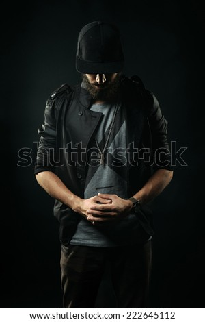 The brutal bearded man in a black jacket stands with his head bowed and holding hands clasped - stock photo