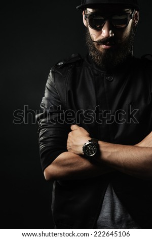 The brutal bearded man with black fitted hat folded his arms across his chest - stock photo