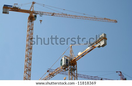 The building crane on a background of the blue sky - stock photo