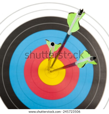 The bull's eye of an archery target hit by three arrows in a square frame