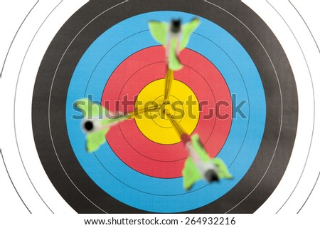 The bull's eye of an archery target with three arrows in short depth of field