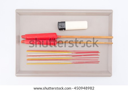 The bunch of incense sticks three types gold, silver and pink gold, two red candle ceremony Chinese candles,  and a lighter  on a tray.  It's burned to intend as a sacrificial offering to various - stock photo