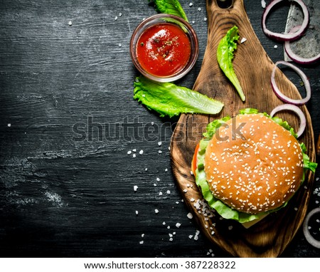 The Burger and the fresh ingredients on the old Board. On a black chalkboard.  Top view. - stock photo