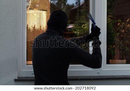 The burglar trying to break into someone's home - stock photo