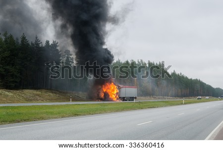The burning truck on the road - stock photo