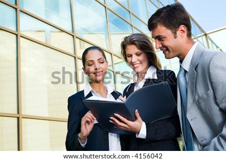 The business women signs the agreement with her partners on a background of a building