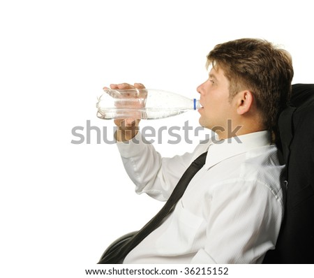The businessman drinking water from a bottle. It is isolated on a white background - stock photo
