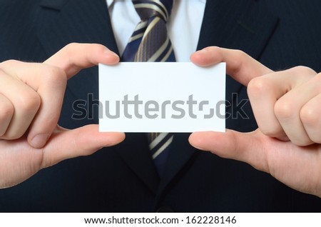 The businessman in a business suit with a visiting card - stock photo