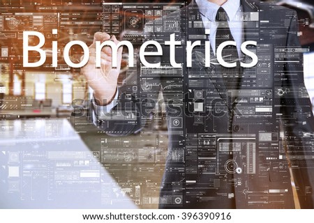 the businessman in the office is writing on the transparent board: Biometrics - stock photo