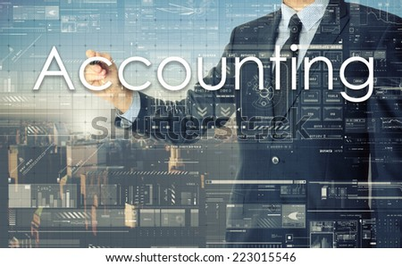 the businessman is writing Accounting on the transparent board with some diagrams and infocharts with the city in the background - stock photo