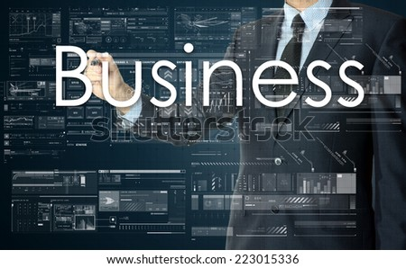the businessman is writing Business on the transparent board with some diagrams and infocharts with the dark elegant background - stock photo