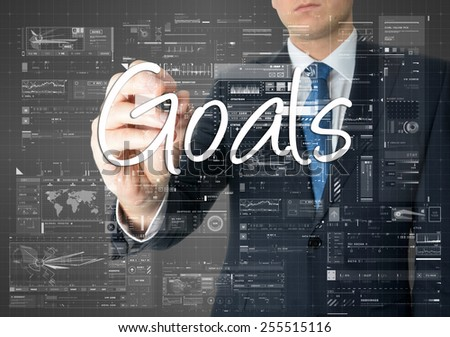 the businessman is writing Goals on the transparent board with some diagrams and infocharts - stock photo