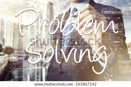 the businessman is writing Problem Solving on the transparent board with some diagrams and infocharts - stock photo