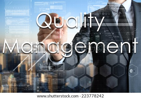 the businessman is writing Quality Management on the transparent board with some diagrams and infocharts with the city in the background  - stock photo
