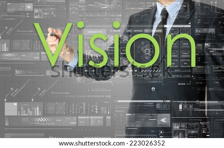 the businessman is writing Vision on the transparent board with some diagrams and infocharts with the dark elegant background