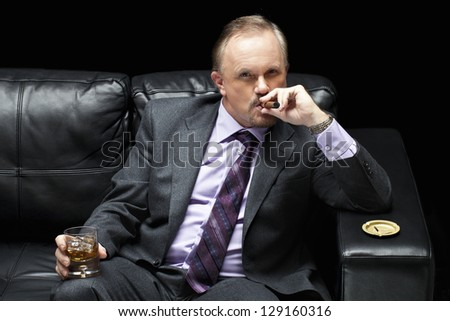 The businessman sipping the cigarette and holding the alcohol drink on a black sofa