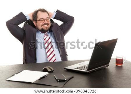 the businessman sits at office table with the laptop