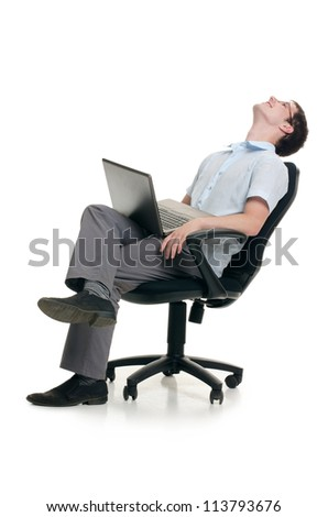 The businessman sits in armchair with laptop