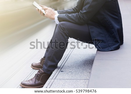 The businessman sitting on stairs and using smartphone