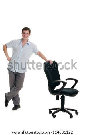 The businessman stands at an armchair isolated