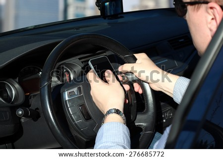 The businessman using  mobile smart phone while driving the car - stock photo