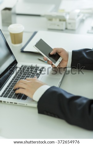 The businessman who operates a smartphone - stock photo