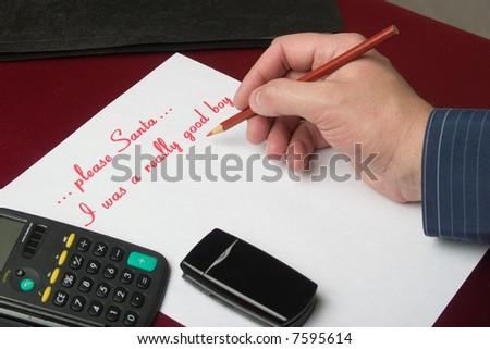 The businessman writes the letter to the Santa. - stock photo