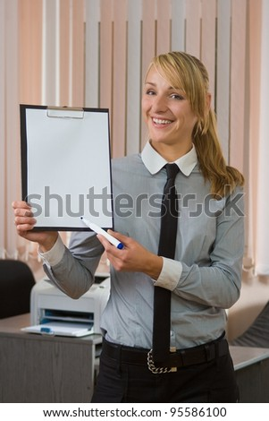 The businesswoman at office shows clipboard in hand