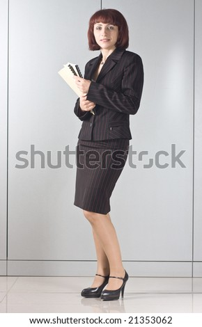 The businesswoman with folders in hands  at a wall - stock photo