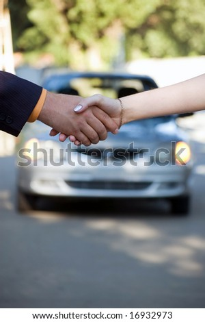 The buyer and the seller shake hands. Car sale