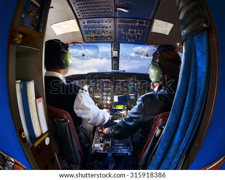 The cabin of the old passenger plane with pilots, mountains and sky outside the window - stock photo