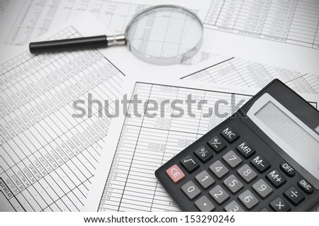 The calculator and magnifier on documents. - stock photo