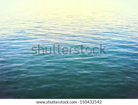 The calm surface of the Pacific ocean with cross-processed colors.  Image displays a distinct paper grain and texture at 100 percent. - stock photo