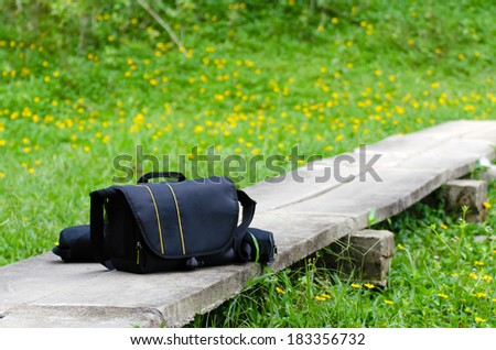 The Camera bag on the yellow daisy and grass field - stock photo