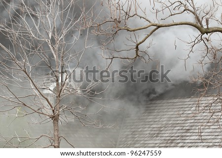 The camera captured this very smokey house fire just before it burst into flames. - stock photo