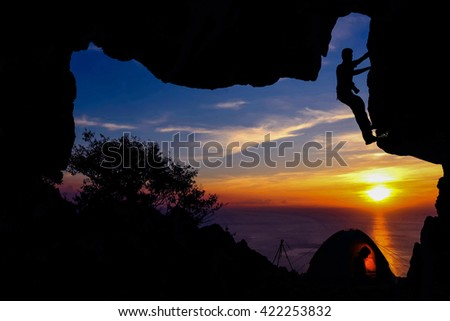 The Camping in front of the cave on the mountain and a man with camera climbing on the cave rock at sunset.