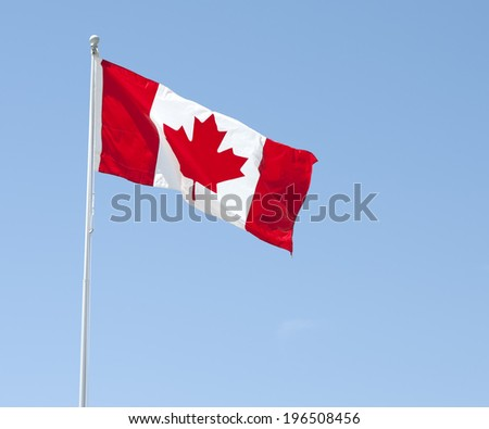 The Canadian flag waving in the breeze under a blue sky. - stock photo
