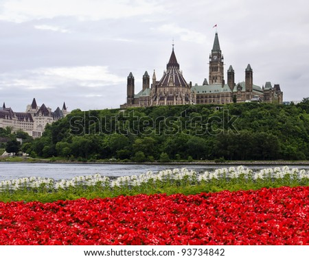 The Canadian Parliament with red and white flowers across the river in Gatineau at 8 O'clock. - stock photo