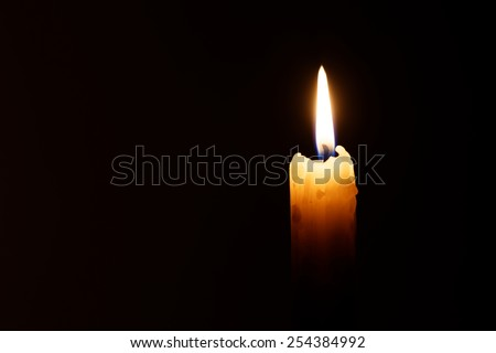The candle's image is isolated against a black background and fades into a shadow.  - stock photo