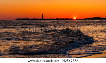 The Cape May Point Lighthouse and waves on the Atlantic at sunset, seen from Cape May, New Jersey. - stock photo