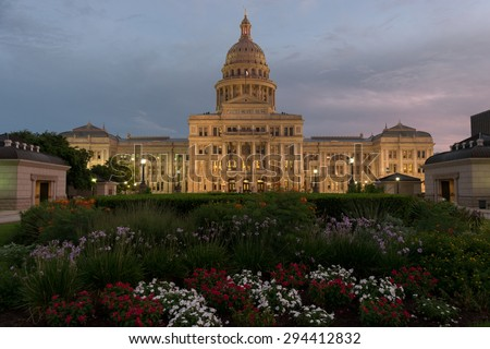 The Capitol Building in Austin, Texas with colorful flower beds in the foreground, lit up by street lights as the sun sets and a cloudy sky grows dark as dusk. - stock photo