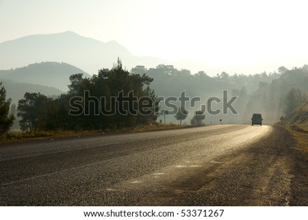 The car going on a line in a morning fog. - stock photo