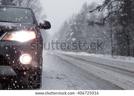 the car stopped at the curb during snowfall - stock photo