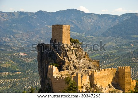 The castle of Cazorla in Andalusia, Spain against a landscape of olive trees