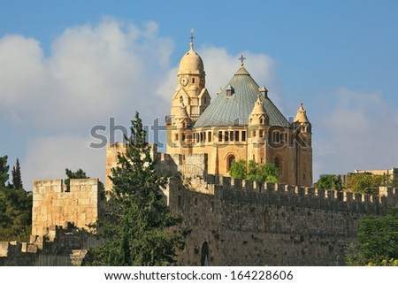 The Catholic Church of Dormition in Jerusalem. The morning sun illuminates the dome and the tower of the abbey. Battlements of Jerusalem surrounded by majestic building - stock photo