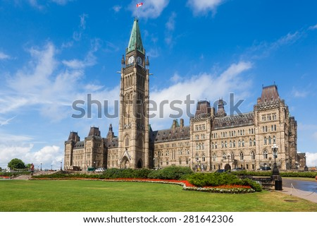 The Center Block and the Peace Tower in Parliament Hill, Ottawa, Canada. Center Block is home to the Parliament of Canada. The central green lawn and the red flowers  front the iconic building. - stock photo